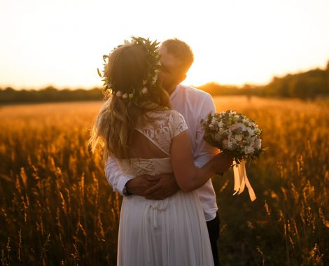 man-and-woman-standing-in-front-of-brown-grass-field-kissing-1573007